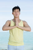 Asian Man doing yoga on a beach. Royalty Free Stock Image