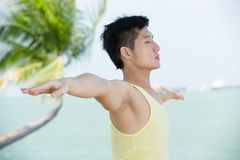 Asian Man doing yoga on a beach. Royalty Free Stock Images
