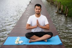 Asian man doing Yoga lotus post. Young Asian smile handsome man, 20-30 years old, Doing Yoga meditation exercise by lotus pose on wooden bridge above peaceful Stock Images