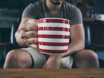 Man drinking hot coffee tea or cocoa. stock photos