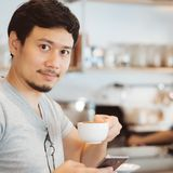 Man is drinking hot coffee in the coffee cafe. stock photos