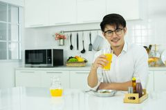 An asian man is drinking orange juice in the kitchen royalty free stock photo