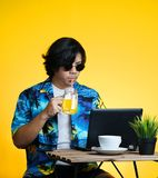 Asian Man Drinking Orange Juice While Working With Laptop on Sum. Mer Vacation Season Against Yellow Background Stock Images