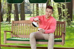 Asian man drinking tea in garden Royalty Free Stock Image