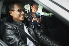 Asian man driving passenger car and woman with smart phone in hand toothy smiling with happiness face royalty free stock photo