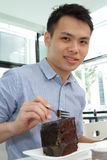 Asian man eating chocolate cake Stock Image
