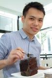 Asian man eating chocolate cake Stock Image