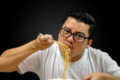 Asian man eating Instant noodles. On black background, with clipping path royalty free stock photos