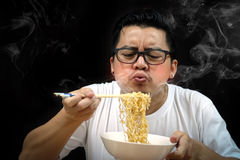 Asian man eating Instant noodles very hot and spicy. On black background stock images