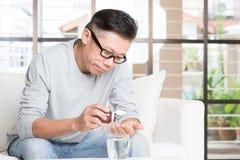 Asian man eating medicine Royalty Free Stock Photo