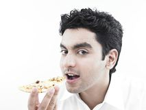 Asian man eating a slice of pizza Stock Photography