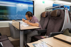 Asian man eating on a train Stock Photos