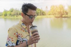 Free Asian Man Enjoying Drink Coffee Cold In Pastic Glass Take Home. Stock Image - 115202601