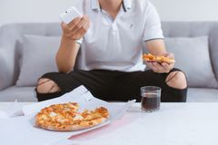 Asian man enjoying his pizza while sitting on couch watching tv stock image