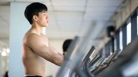 Asian man exercise on elliptical trainer machine. At gym stock footage