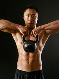 Asian man exercising with kettlebell Royalty Free Stock Photo