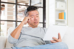 Asian man with eyes problem. After long hours of using computer tablet Stock Photos