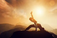 Asian man, fighter practices martial arts in mountains. Asian man, fighter practices martial arts in high mountains at sunset. Kung fu and karate pose. Also Royalty Free Stock Photo