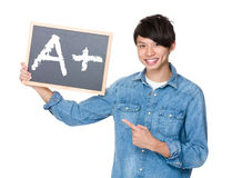 Asian man finger point to chalkboard and showing A plus mark Royalty Free Stock Photos
