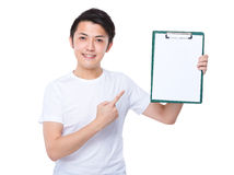 Asian Man with finger point to white paper of clipboard Royalty Free Stock Photo