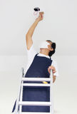 Asian Man Fixing Light At Home. Royalty Free Stock Photography