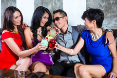 Asian man flirting with women in nightclub. Asian young and handsome party people men flirting with women in fancy night club stock image