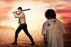 Asian man with formal wear holding stick bat want to hit zombie Stock Photo
