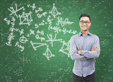 Asian man and formulas on chalkboard Stock Image