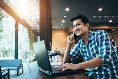 Free Asian Man Freelance Work On Computer Touch Pad While Talking On Smart Phone With A Happy Smile, Young Business Man Use Laptop Royalty Free Stock Image - 149718276