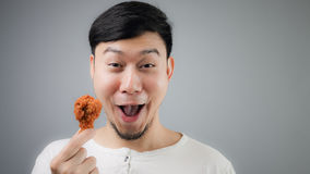 An Asian man with fried chicken. Royalty Free Stock Image