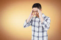 Asian man getting a headache. On white background royalty free stock photography