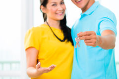 Asian man giving girlfriend key to move in new home Stock Photography