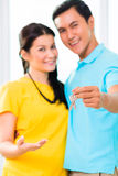Asian man giving girlfriend key to move in new home Stock Images