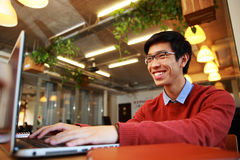 Asian man in glasses typing on laptop. Cheerful asian man in glasses typing on laptop in office stock images
