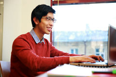 Asian man in glasses working on laptop Royalty Free Stock Photos