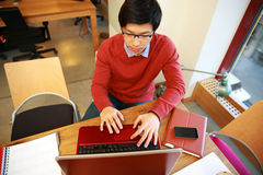 Asian man in glasses working on laptop Royalty Free Stock Images
