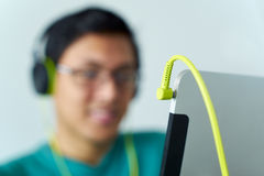 Asian Man With Green Headphones Listens Podcast Tablet PC. Chinese man relaxes on sofa and watches podcast on tablet pc, listening with green big earphones Royalty Free Stock Image