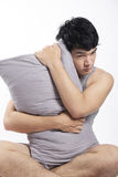 Asian man in grey pajamas sitting and holding the pillow Stock Images