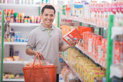 Asian man in grocery store. Asian man buy some stuff at supermarket royalty free stock images