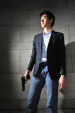 Asian Man with a Gun standing in the shadow royalty free stock image