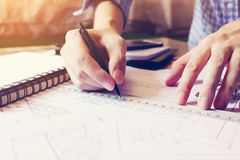 Asian man hand drawing on blueprint paper at home office. stock photos