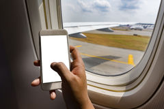 Asian man hand holding smart phone  on board of airplane near window seat and wing Royalty Free Stock Photo
