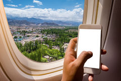 Asian man hand holding smart phone  on board of airplane near window seat and wing Royalty Free Stock Image