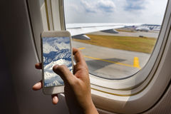 Asian man hand holding smart phone  on board of airplane near window seat and wing Royalty Free Stock Photography