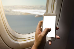 Asian man hand holding smart phone  on board of airplane near window seat and wing Royalty Free Stock Images