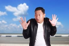 Asian Man with Hands Up Surrender. Portrait of funny young Asian man wearing black leather jacket shows hands up surrender gesture, over cloudy blue sky Stock Image