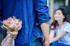Asian man has preparing and waiting with flower for say sorry an. Asian men has preparing and waiting with flower for say sorry and apologies to girlfriend royalty free stock image