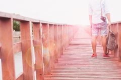 Asian man in hat with backpack traveling on bridge to the sea. Summer travel Stock Photography