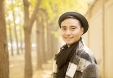 The Handsome Asian man smiles in the autumn park. Asian man in hats outdoors royalty free stock photos