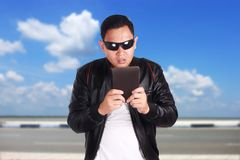 Asian Man Having Surprising News on Tablet. Portrait of attractive young Asian man wearing black leather jacket and sunglasses looking surprising online news on Stock Images